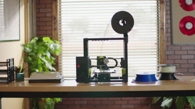 Digital model rotates on computer screen as camera pans to 3D printer manufacturing object in modern office.