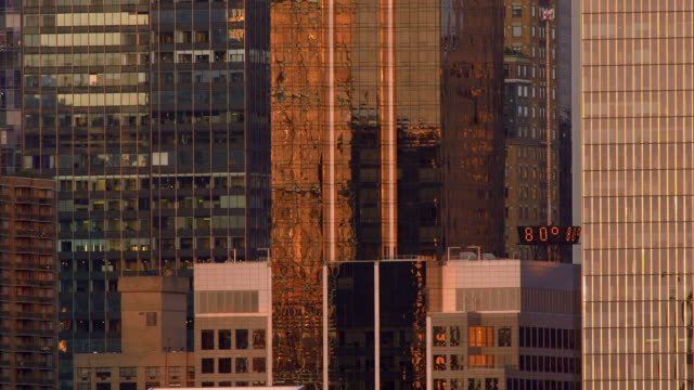vidéos et rushes de digital sign surrounded by new york city skyscrapers reflecting the setting sun - effet miroir