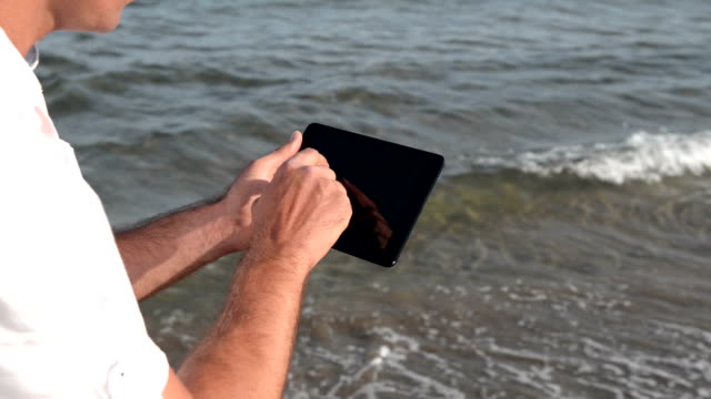 digital tablet at the beach - white shirt stock videos & royalty-free footage
