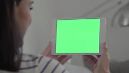 Digital tablet chromakey, woman close up on a sofa.