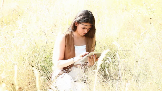 Digital tablet girl, outdoors in long grass.