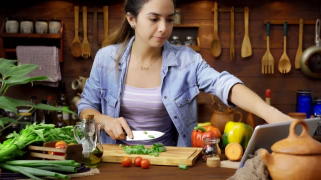 digital tablet recipe: dolly shot of hispanic young woman chopping vegetables for preparing food - preparing food stock videos & royalty-free footage