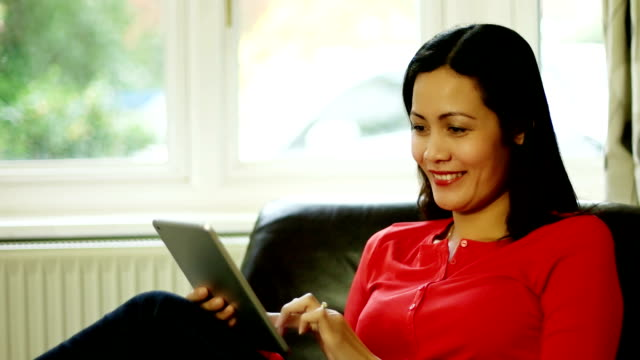 Digital tablet, relaxing at home. SE Asian woman. MS DS
