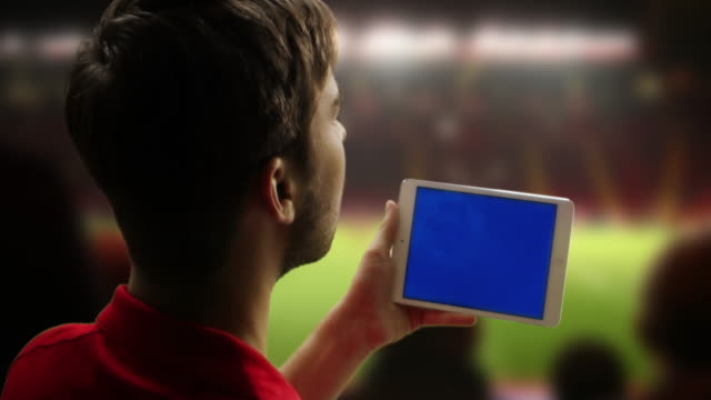tablet Digital de desporto ventoinha no jogo. Chromakey ecrã.
