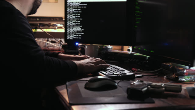 Digital threat by male cyber criminal computer hacker typing code while trying to break into a computer network during the day - a gun lies on the table besides him. He enters the frame in the beginning and leaves the frame in the end.