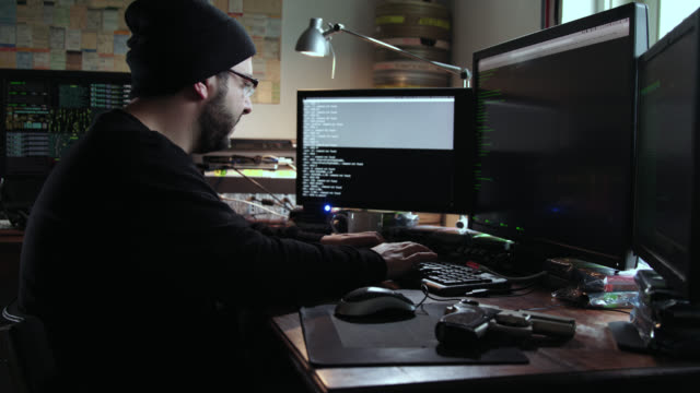 digital threat by male cyber criminal computer hacker typing code while trying to break into a computer network during the day - a gun lies on the table besides him. - hacker stock videos and b-roll footage