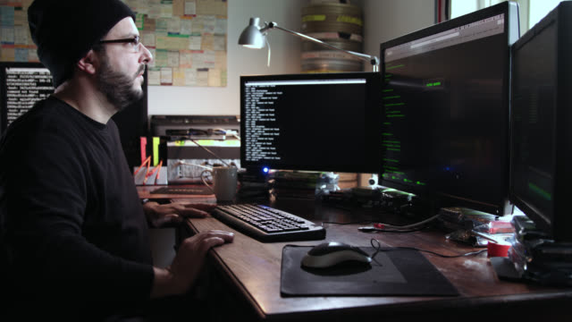 digital threat by male cyber criminal computer hacker typing computer code while trying to break into a computer network during the day – he leaves the frame in the end. - chairperson stock videos & royalty-free footage