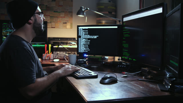 vídeos de stock, filmes e b-roll de digital threat by male cyber criminal computer hacker typing computer code while trying to break into a computer network during night – he enters the frame at beginning. - deep web