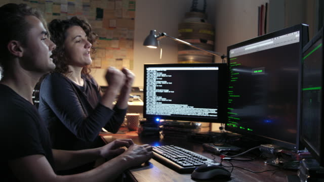 digital threat - nerdy female computer hacker and a young male computer geek typing computer code in computer language while trying to break into a secured computer network during night - both leaving the frame in the end after being happy successful. - hacker stock videos and b-roll footage
