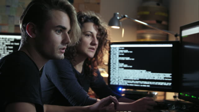 Digital threat - nerdy female computer hacker and a young male computer geek typing together computer code in computer language while trying to break into a secured computer network during night.