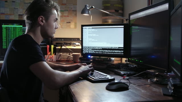 digital threat - nerdy young male computer hacker geek typing computer code in computer language while trying to break into a secured computer network during nigh – close shot – he leaves the frame in the end. - coding stock videos & royalty-free footage
