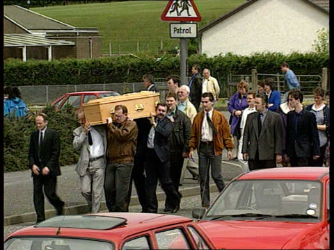 dignam funeral n ireland portadown ls hearse along slowly as mourners along behind ls mourners as carrying coffin along pan rl cms claire dignam as... - priest stock videos & royalty-free footage