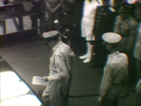 W HA COMPOSITE Dignitaries and army officer signing treaty on table on board of naval vessel during Japanese surrender