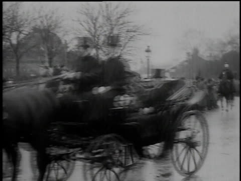 Dignitaries and leaders riding in horsedrawn carriages on rainy street / Paris France