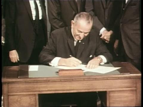 vidéos et rushes de dignitaries surround president lyndon b. johnson as he signs a bill. - 1968