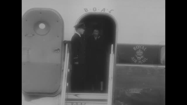Dignitaries wait for Elizabeth II on tarmac / Winston Churchill right profile / she appears in open doorway of BOAC airplane as man salutes her...