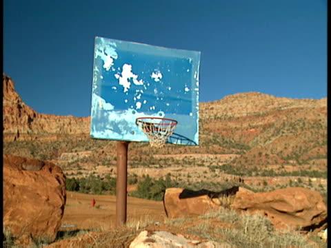 Dilapidated outdoor basketball hoop w/ discolored light blue backboard red green grass field BG Mohave County Arizona Strip AZ