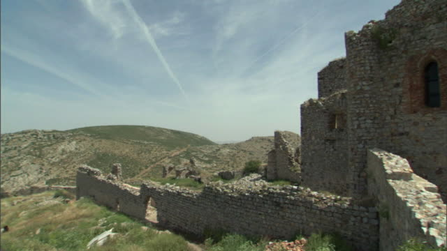 ms, pan, dilapidated walls and facade of medieval church, aldea del rey, castile-la mancha, spain - spagna video stock e b–roll