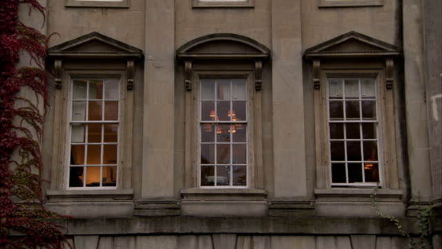 vidéos et rushes de dim light glows in the windows of a townhouse, bath. available in hd. - fronton