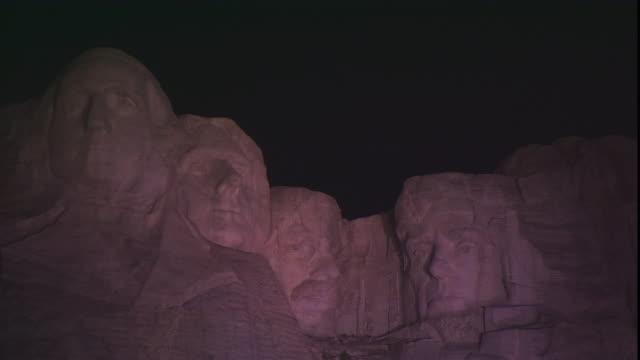 dim light illuminates mount rushmore at night. - mt rushmore national monument stock videos & royalty-free footage