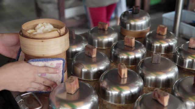 dim sum(chinese cuisine) steaming in bamboo basket. - tipo di panino video stock e b–roll