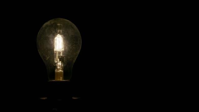 a dim, warm-colored, globe-shaped lightbulb on a black background - cavo componente elettrico video stock e b–roll