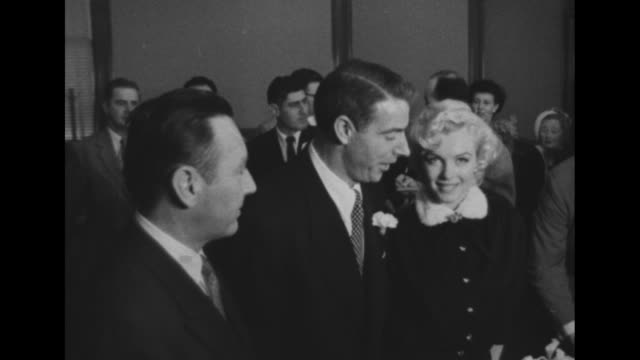 stockvideo's en b-roll-footage met dimaggio with monroe / the couple in a room with several others and he kisses her / the couple in a car circled with press and cameras / the car... - marilyn monroe