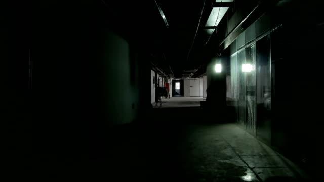 vidéos et rushes de un couloir faiblement éclairé avec une lumière sur - horreur