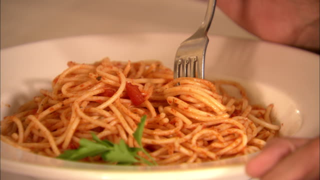 stockvideo's en b-roll-footage met a diner swirls spaghetti onto a fork. - spaghetti