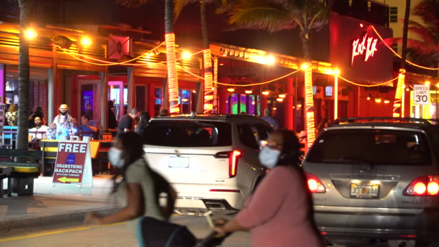 diners and pedestrians some wearing face coverings crowd the sidewalk around rock bar restaurant on fort lauderdale beach boulevard on october 9 fort... - scott mcpartland stock videos & royalty-free footage