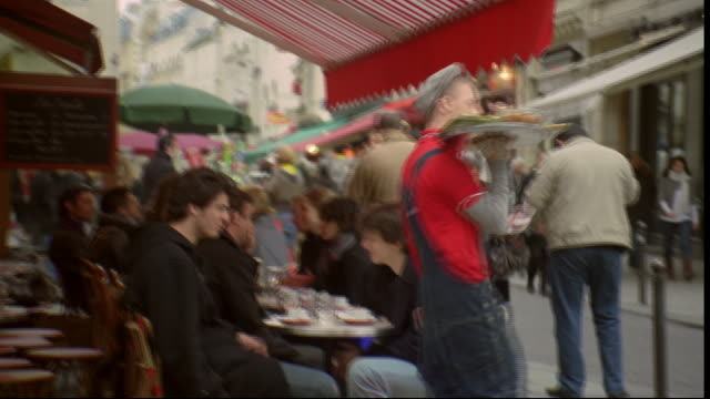 Diners eat at an outdoor cafe in Paris, France.