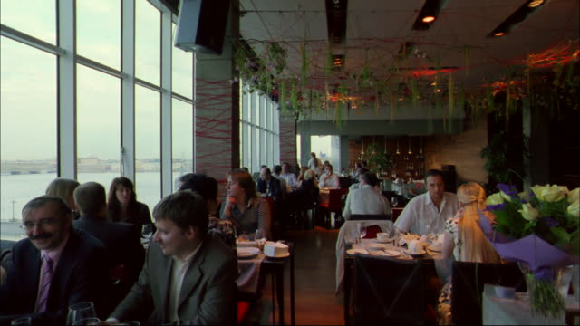 Diners enjoy the luxurious setting of a St. Petersburg restaurant overlooking the water.