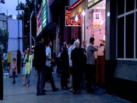 vidéos et rushes de diners waiting in line at food stand, crowds walking around / tehran, iran - format vignette
