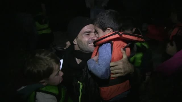 a dinghy carrying emotional migrants lands at night on lesbos shortly after greek premier alexis tsipras toured migrant facilities on the greek... - traditionally austrian stock videos and b-roll footage