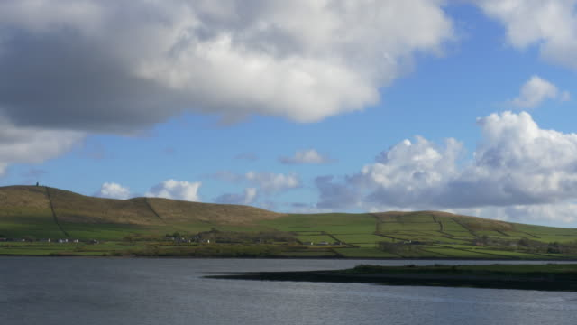 T/L Dingle Harbor, puffy clouds over water and green fields, County Kerry, Ireland