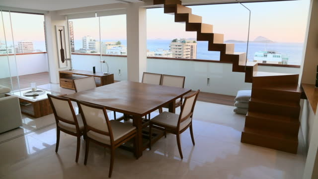 vídeos de stock, filmes e b-roll de dining room of modern apartment with ocean view - mesa mobília