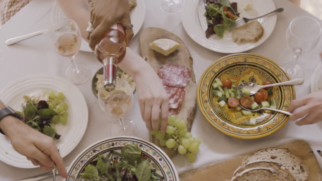 dining table with hands serving, sharing drink and food. - food stock videos & royalty-free footage