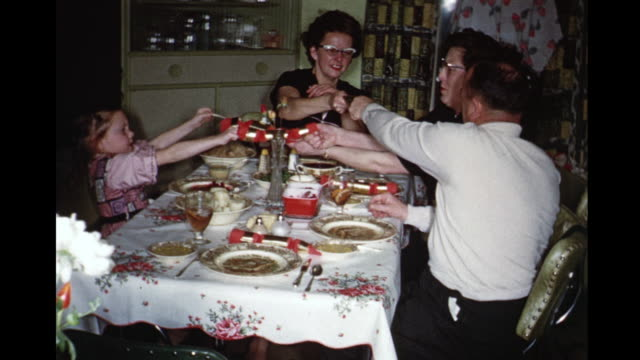 1959 HOME MOVIE Dinner guests pulling on Christmas crackers / Toronto, Canada