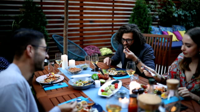 dinner party guests talking at the table and eating - vegan food stock videos & royalty-free footage