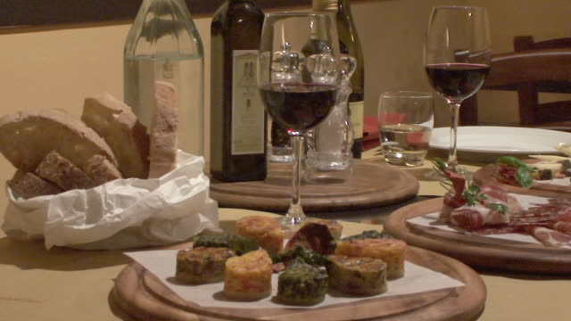 vídeos de stock, filmes e b-roll de ms pan dinner set-up with appetizers in restaurant / lucca, tuscany, italy - italian culture