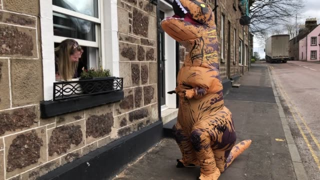 a dinosaur is seen stalking the streets of perthshire town amid coronavirus lockdown the fearsome beast entertained locals in the town of callander - perthshire stock videos & royalty-free footage