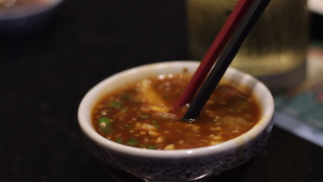 dip boiled pork in a thai sukiyaki sauce in a restaurant - sukiyaki stock videos and b-roll footage