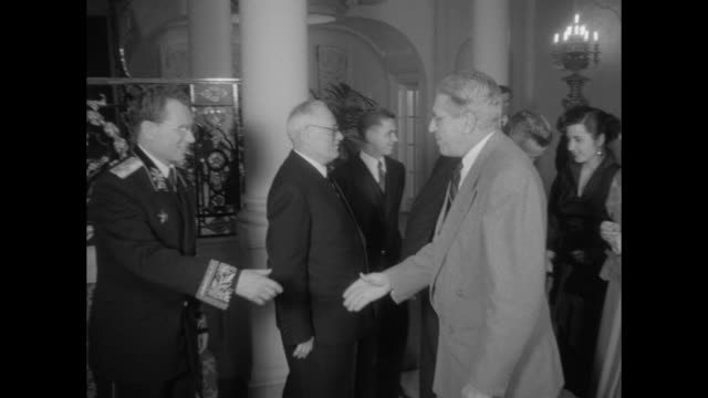 USSR diplomats Andrey Vyshinsky Aleksandr Panyushkin greet dignitaries at receiving line during a reception held at the Soviet embassy in...