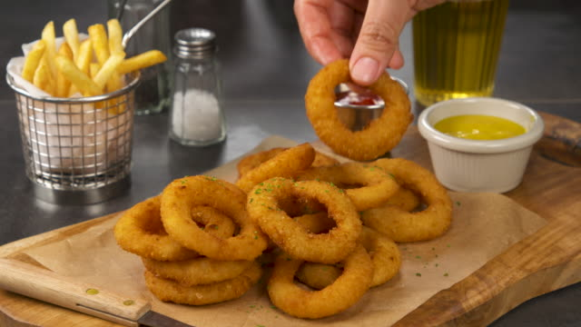 dipping an onion ring into mustard sauce / south korea - mustard stock videos & royalty-free footage