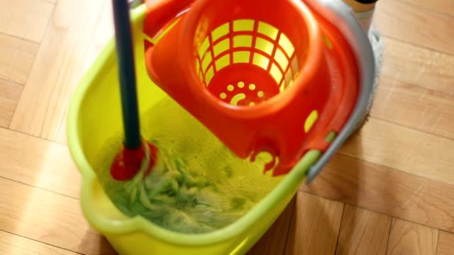 eintauchen des mop in reinigungsflüssigkeit - eimer stock-videos und b-roll-filmmaterial