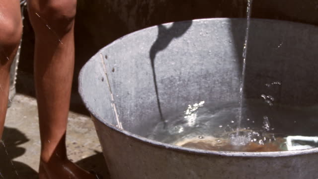 Dipping water out of bucket