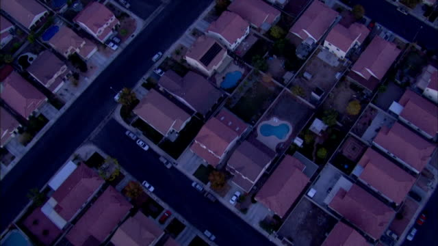 aerial filtered *direct td ws moving over neighborhood houses close together in blocks w/ paved asphalt blacktop roads passing over several open... - home ownership stock videos & royalty-free footage
