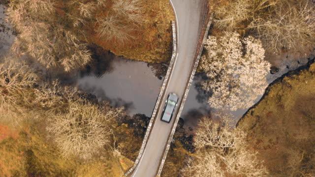 vídeos de stock e filmes b-roll de directly above a bridge road in the scottish highlands - vista de cima para baixo
