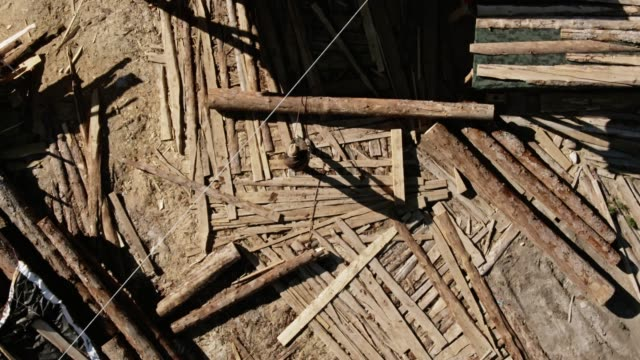 directly above aerial drone shot of a caucasian man in his thirties using a rope to roll a log towards him in a lumberyard on a sunny day next to an outdoor wood shop - lumberyard stock videos and b-roll footage