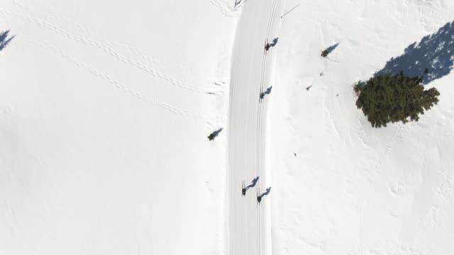 direkt ovanför aerial drone shot av en grupp av fyra vuxna längdskidåkning i en linje på en snöig trail i bergen på en solig vinterdag i colorado - längd bildbanksvideor och videomaterial från bakom kulisserna